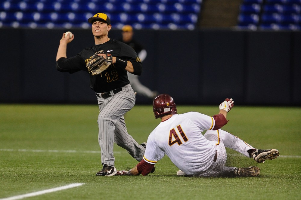Minnesota infielder Dan Olinger slides into second base as Iowa's Jake Mangler throws the ball to first base Friday at the Metrodome.