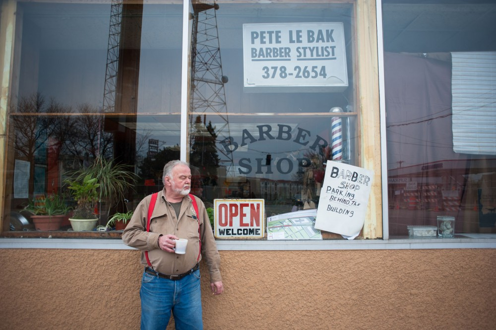 Pete Lebak waits for customers in front of his one-chair barbershop Saturday on University Avenue. Despite a drop in business during light-rail construction, Lebak is determined to keep his shop operating, as he has done for the last 32 years.