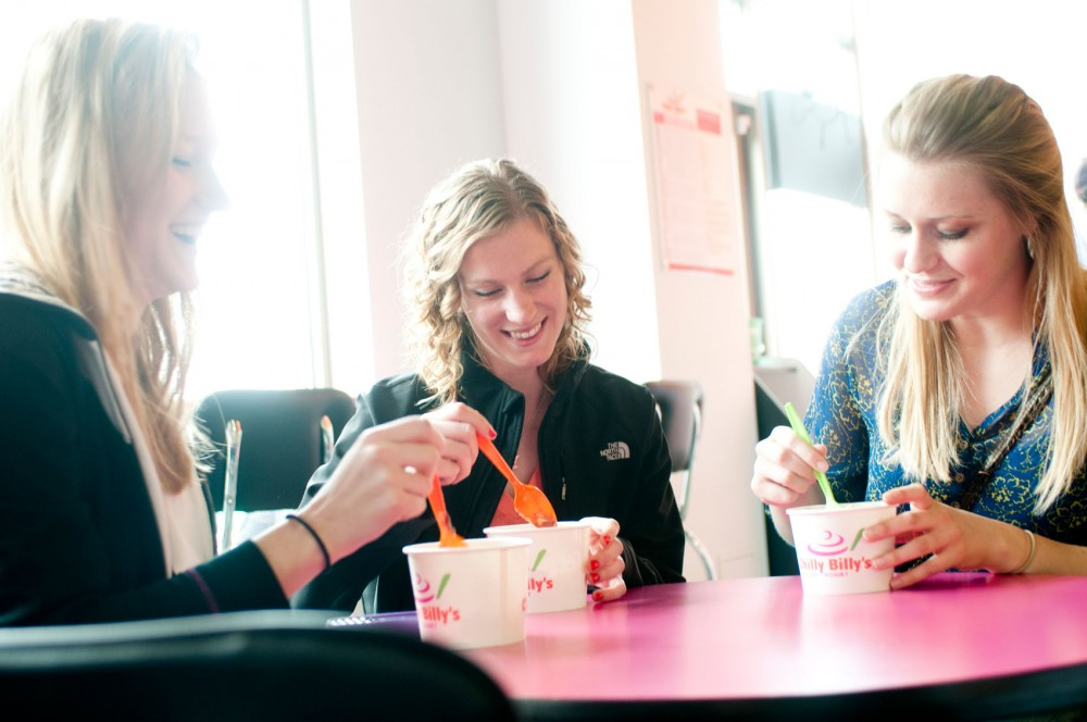 Kinesiology junior Kristin Tyler, strategic communications junior Elli Norberg and biology junior Colleen Mooney, from left to right, enjoy frozen yogurt Monday at Chilly Billy's. The Dinkytown frozen yogurt shop celebrated its first anniversary with 50 percent off all frozen yogurt creations.