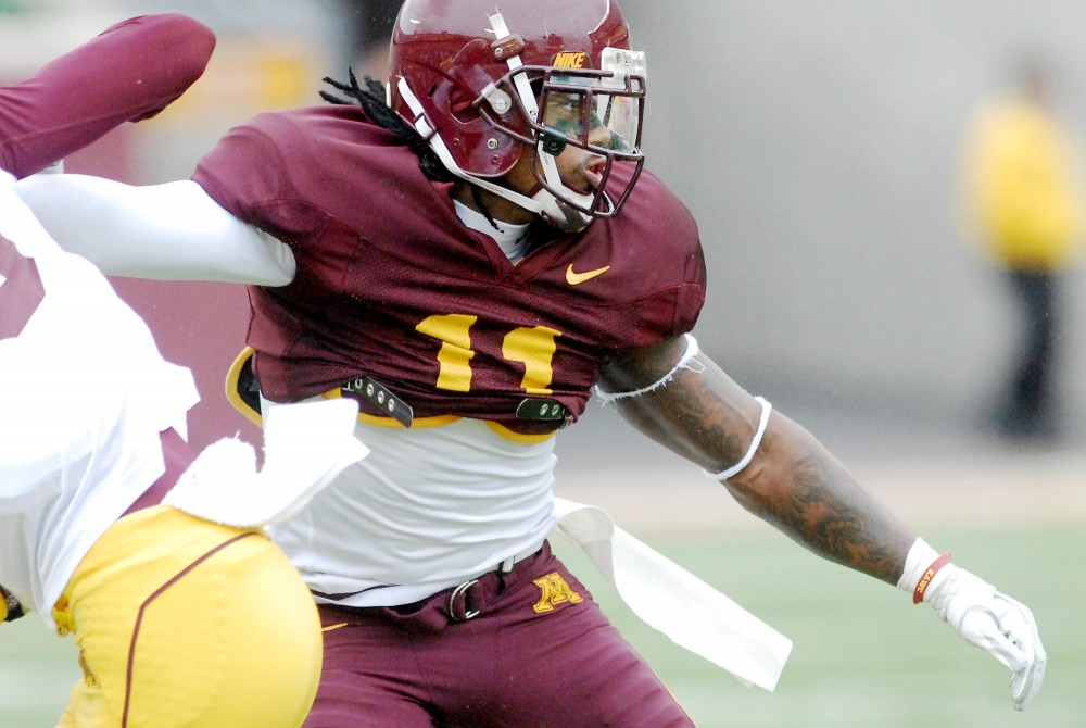 Minnesota defensive back Troy Stoudermire jams a receiver from the Gold team during Saturday