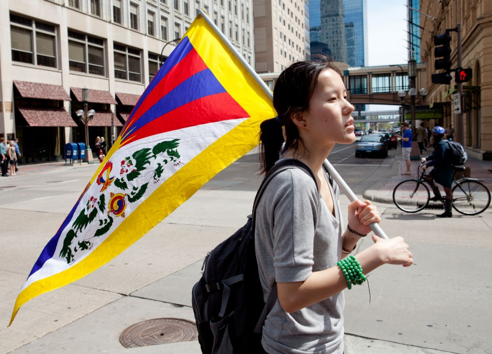 Political science and global studies senior Tenzin Pelkyi holds the Tibetan flag as she and her colleagues collect signatures for a petition to support the release of the 6-year-old Panchen Lama on Wednesday in downtown Minneapolis.