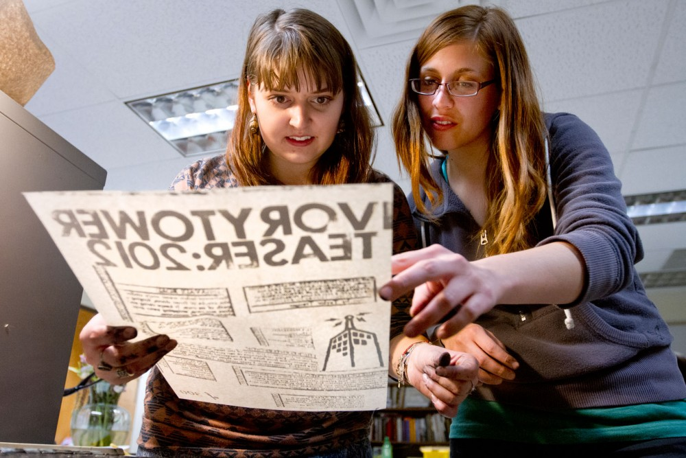 Taylor Trauger, a junior majoring in English and French, and Jen Rosenberg, a senior majoring in theater and English, look over a handmade poster for the Ivory Tower magazine teaser on Monday night in the basement of Lind Hall.