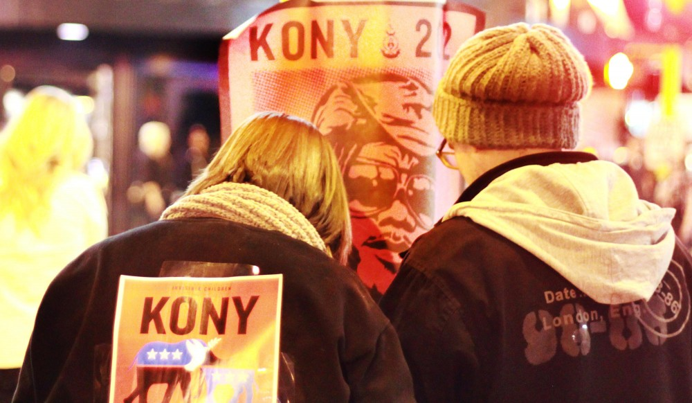 Cover the Night participants Emily Johnson, left, and Erik Johnson work as a team to put up several posters for KONY 2012 on Friday in the downtown area. They were part of a larger group that put up posters in various parts of Minneapolis.