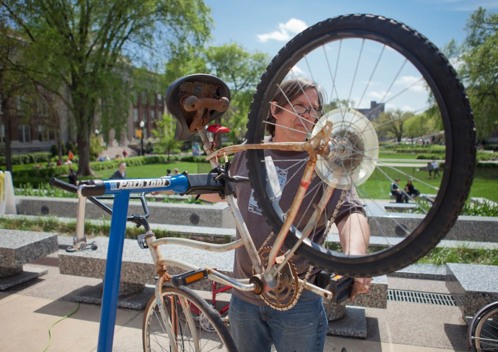 "Self-described grease monkey Brent Fuqua uses parts from other cycles that have been abandoned or confiscated to put together a bike Tuesday in front of Northrop. Re-Cycle assembles these ""Frankenstein"" bikes and sells them to the public at a cheap price."