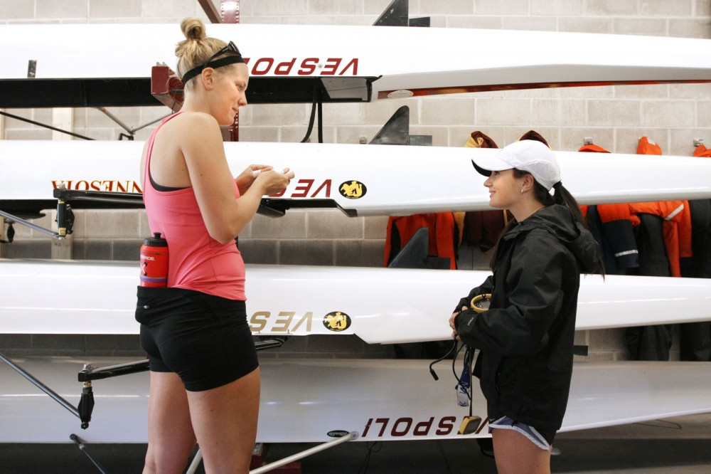 At 4-foot-11, coxswain Jackie Stein talks to Leah Rogotzke before practice Tuesday at the boat house. Traditionally, there is a lot of pressure for coxswains to be petite.