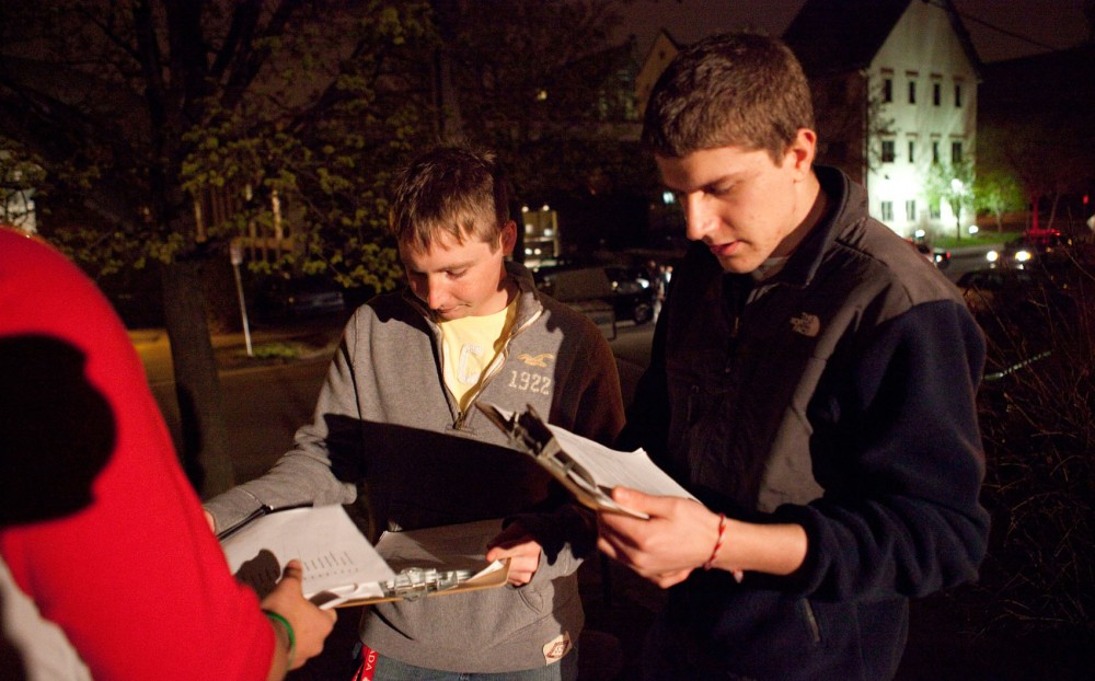 Arkeo volunteers Anthony Pirkl and Stefan Platikanov review their checklist to make sure fraternities are fulfilling their regulatory obligations to oversee social events Saturday night on University Avenue. Each Friday and Saturday night, volunteers of the greek party-patrol program visit University of Minnesota fraternities to enforce Interfraternity Council policies.