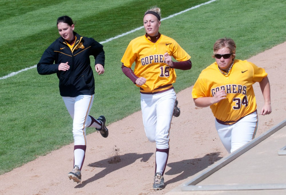 Gophers softball utility players Josie Solie, Alex Pafko and Sara DuPaul, from left to right, run alongside the field during a Sunday afternoon game against Nebraska. Solie and Pafko, both Gophers soccer players, are now pinch runners for the Gophers softball team.