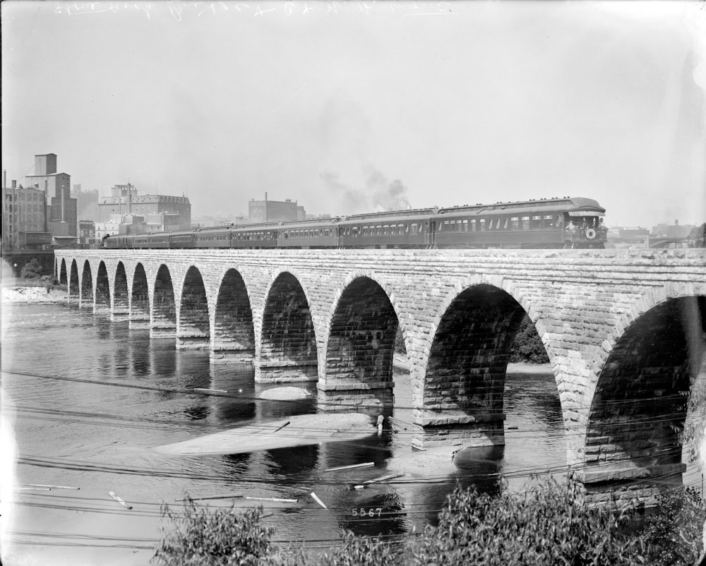 A passenger train crosses the Stone Arch Bridge in 1915. It served as a working railroad bridge until 1978, and became a pedestrian and bike trail in 1994.