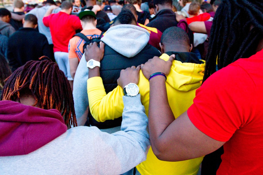 Students, friends and family of recently passed Minnesota linebacker Gary Tinsley gather and hold a group prayer Friday night outside of Roy Wilkins Hall.