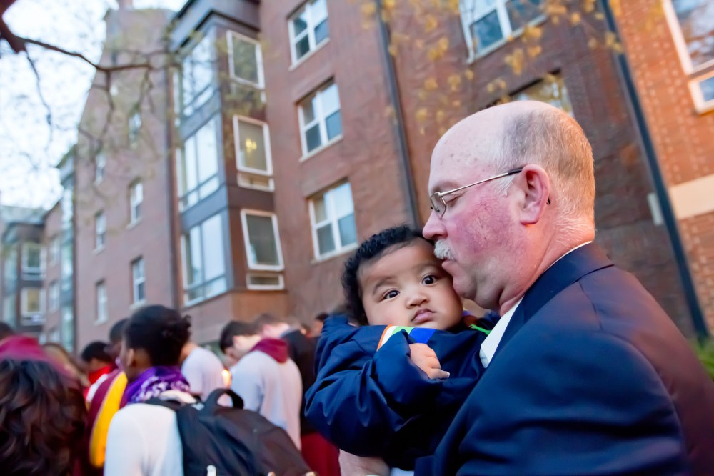 Minnesota head football coach Jerry Kill holds quarterback MarQueis Gray's son during the Friday night vigil for linebacker Gary Tinsley held outside of Roy Wilkins Hall.