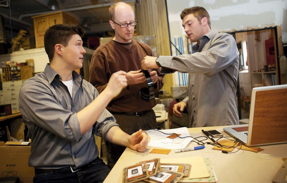 Kevin Groenjes, boB Feyereisen, and Benjamin VandenWymelenberg work on the design of their upcoming product, Woodchuck for Beats by Dr. Dre, on Sunday near the Southeast Como neighborhood. VandenWymelenberg and Groenjes, who are seniors at the University, create wood cases for iPhones, Macbooks, and iPads.