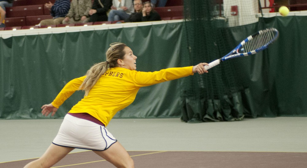 Gophers junior Doron Muravnik lunges for the ball Sunday during a game against the University of Iowa at the Baseline Tennis Center.
