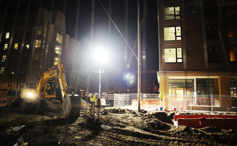 Construction workers continue work on the Central Corridor light rail line late into the night at the intersection of Washington Avenue and Ontario Street South East.
