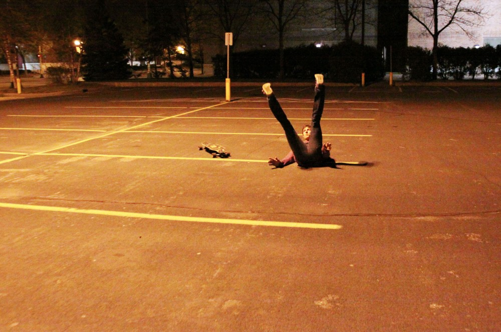 Sophomore Kyle Senger takes a tumble on his longboard outside Williams Arena early Thursday morning.