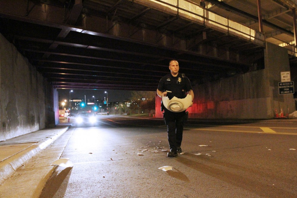 Officer Luke Huck of the UMPD picks of remnants of a plastic light dome that was throne over the Washington Avenue bridge onto the East River Parkway.