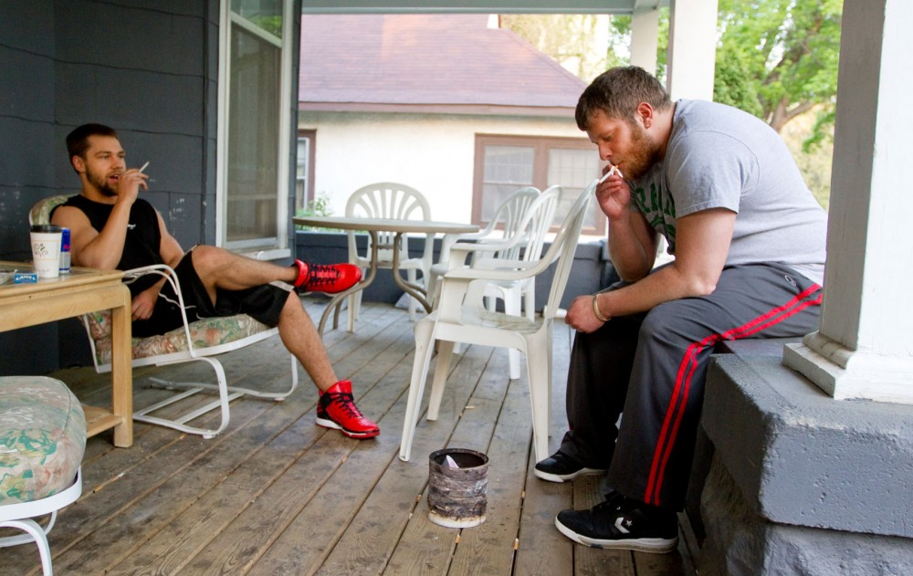 Cody Lake, left, and roommate Nick Fehst smoke a cigarette on the porch of University House, a sober house in Marcy-Homes neighborhood. Lake will start taking classes at the University this summer.