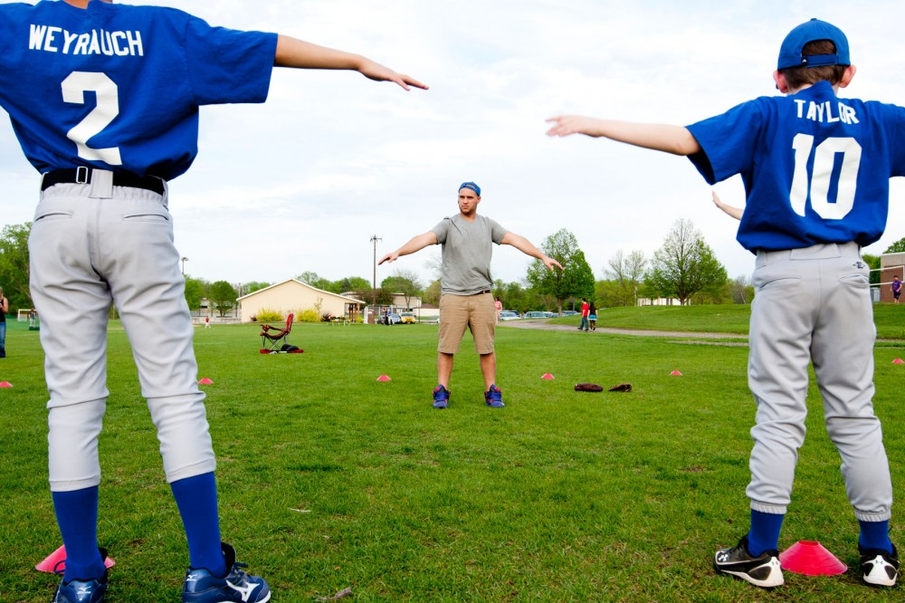 History senior Steve Porter stretches with the Plymouth Wayzata Youth Baseball team during practice Wednesday at the Wayzata East Middle School.