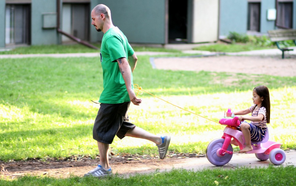 Religious studies graduate Carl Moerschbacher pulls his 5-year-old daughter Aliyah on Monday in the courtyard of the Como Student Community Cooperative during a family Memorial Day barbecue. Moerschbacher and his wife, a student at Minneapolis Community and Technical College, have four children ranging from age 1 to 6.