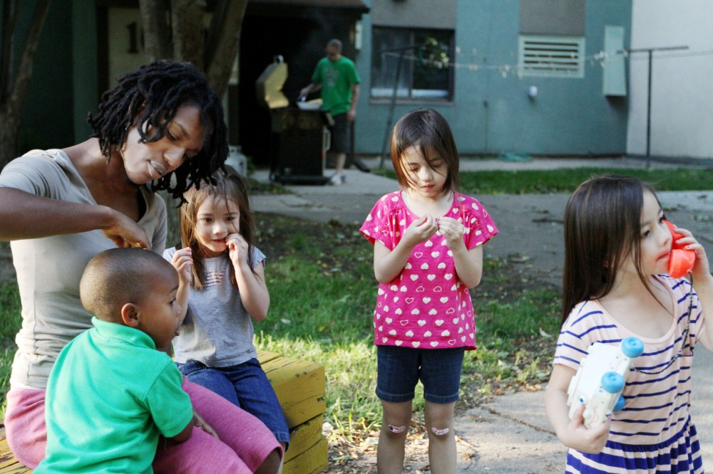 Carl Moerschbacher's daughters, Aliza, Aida and Aliyah, spend time in the courtyard of the Como Student Community Cooperative with culture and teaching doctoral candidate Shelda Smith and her son, Elijah on Monday.