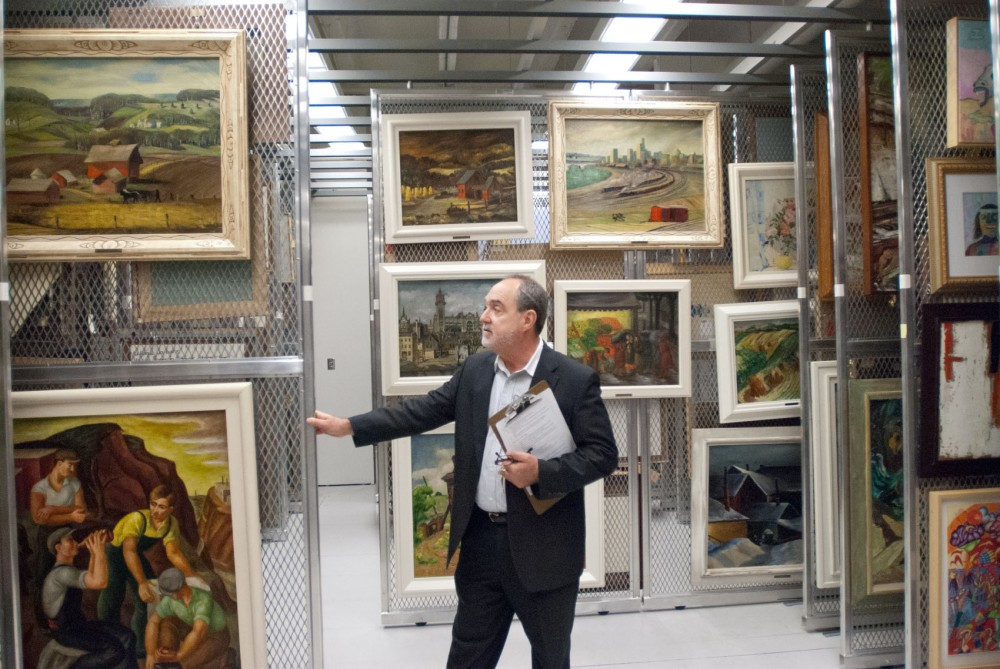 Brian Szott, head of collections at the Minnesota Historical Society, shows paintings from the Public Works of Art Project onThursday in the History Center archives.