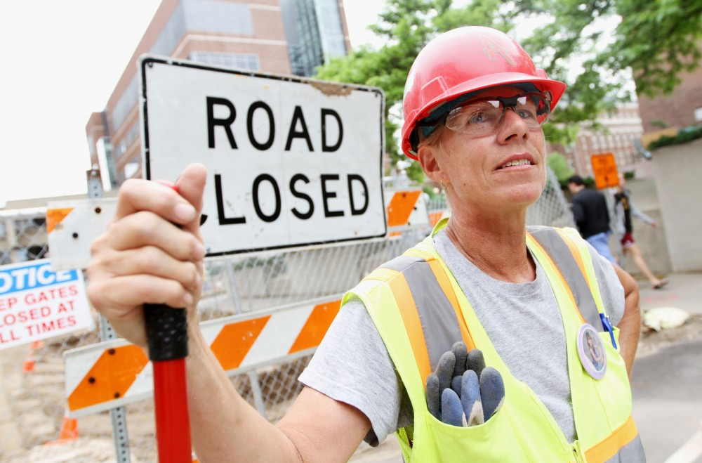 Jenellen Gallatin, a laborer with Ames Construction, finishes up her work clearing roads, adjusting signs and moving gates May 25 on Union Street Southeast.