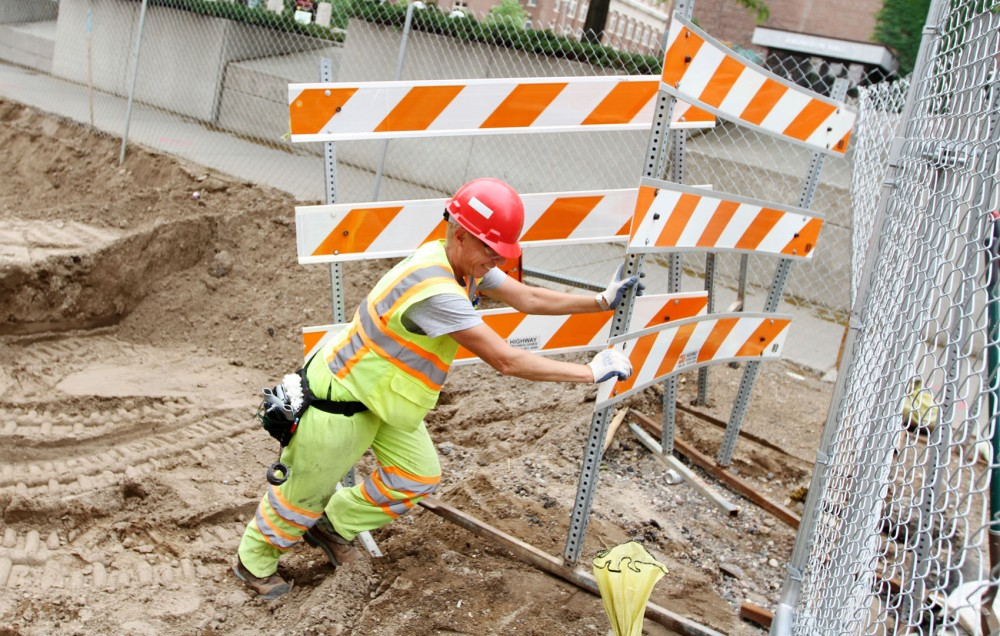 Laborer Jenellen Gallatin clears constructions signs from in front of a gate May 25 on Union Street Southeast.