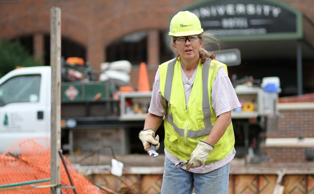 RailWorks laborer Lisa Becker measures and surveys to put in light-rail tracks May 25 on Washington Avenue Southeast.