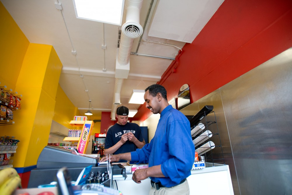 Ahmed Mohamed, owner of the newly opened U of M Market, rings up a customer in his store Friday. Mohamed is a native of Eritrea and is a new father of three.
