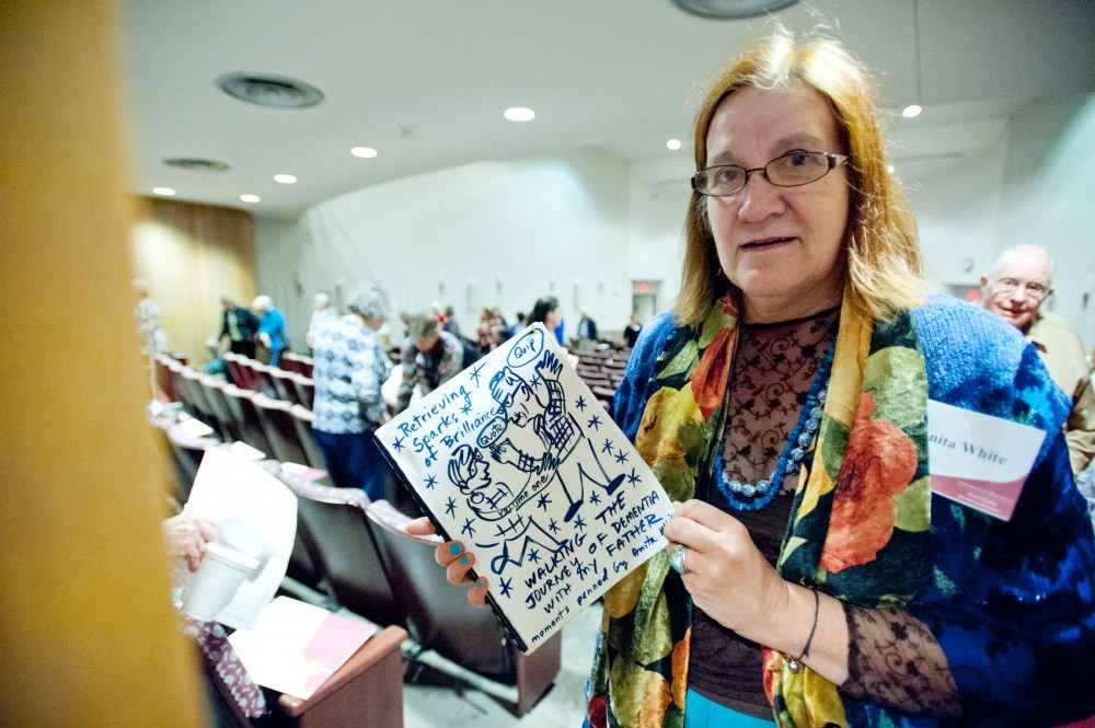 Anita White holds the journal she has created while caring for her 87-year-old father, who has dementia, at the Mayo Auditorium on Saturday. White was inspired to journal from her experiences dealing with her father's memory loss.