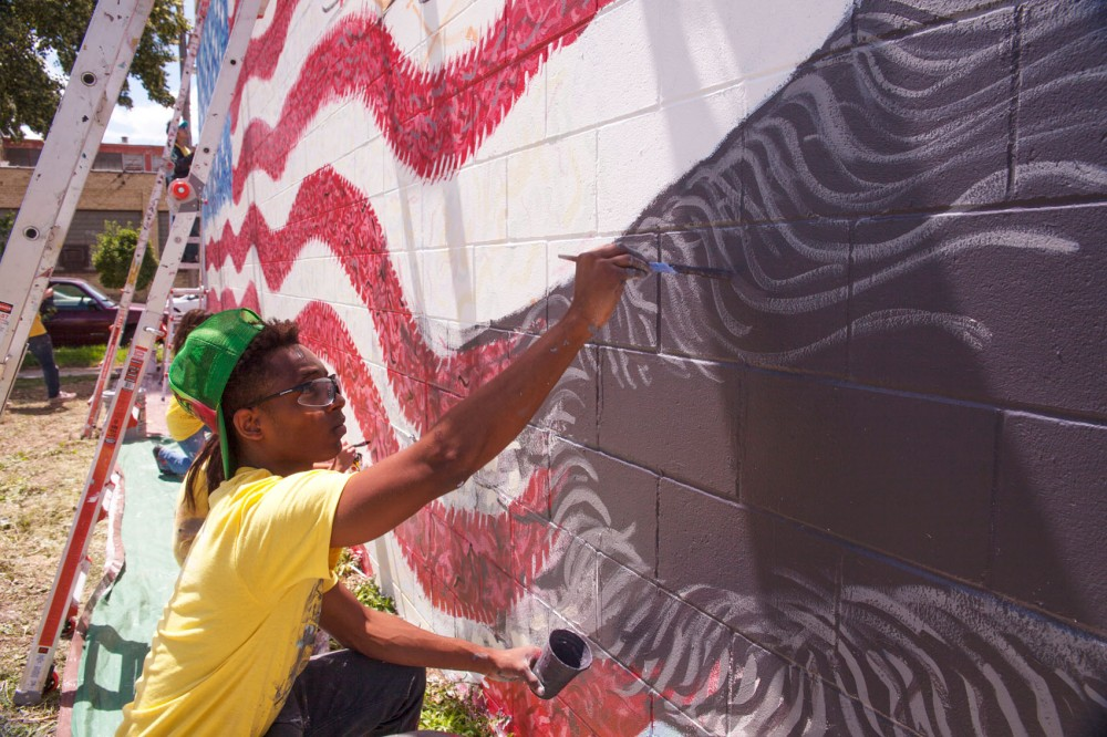 Deonte Lawson paints accents for the eagle's feathers Thursday during the second day of working on a flag mural in South Minneapolis.
