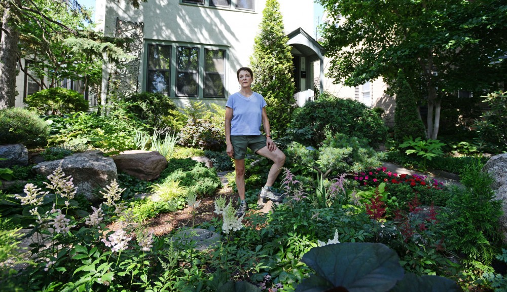 Sonny Schneiderhan stands in her garden Tuesday in front of her Marcy Holmes neighborhood home here she has lived since 1974. Schneiderhan and other long-time residents have expressed frustration with the upkeep of surrounding rental properties.