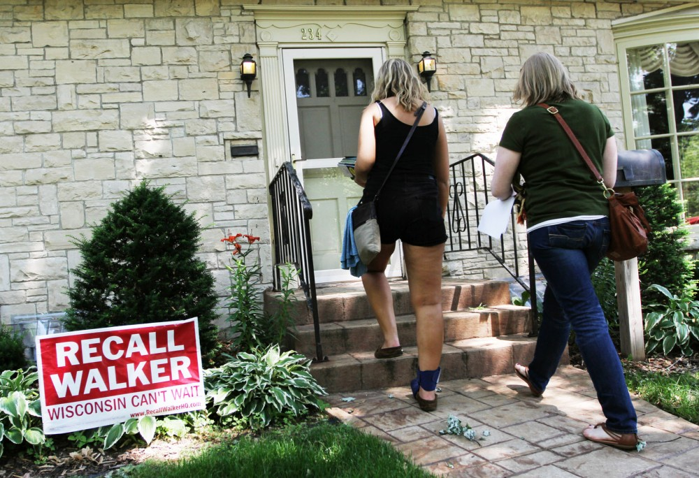 Political science junior Daveen Trentman, left, and Taryn Brown from the DFL knock on doors to persuade voters to get to the polls and vote for Gov. Scott Walkers challenger Tom Barrett Tuesday in Eau Claire, Wis.