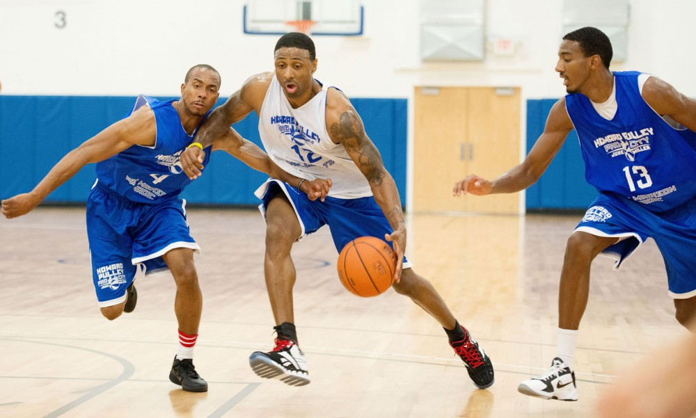 Troy Bell, center, maneuvers the ball away from Ohio State's P.J. Hill, left, and the Gophers' Austin Hollins, right, on Thursday during a pro-am Howard Pulley league game at the High Performance Academy in Eagan, Minn.