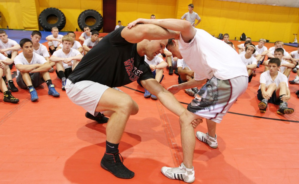 University of Minnesota wrestling and student alum Joe Nord, left, demonstrates a move to young wrestlers of the J Robinson Intensive Wrestling Camp on Wednesday at the Gibson-Nagurski football complex.