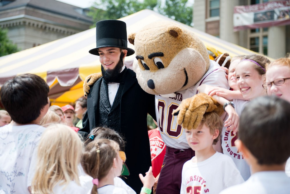 A costumed Abraham Lincoln and Goldy Gopher pose for photos during Land Grant Sesquicentennial Day on Friday on Northrop Plaza.
