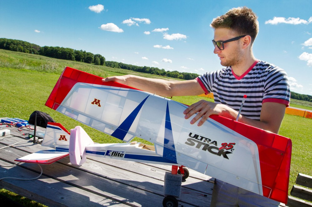 Aerospace engineering and mechanics doctoral candidate Andrei Dorobantu checks the inner hardware of research plane Thor Friday at a hobby field in Anoka, Minn., during experimental flight tests.