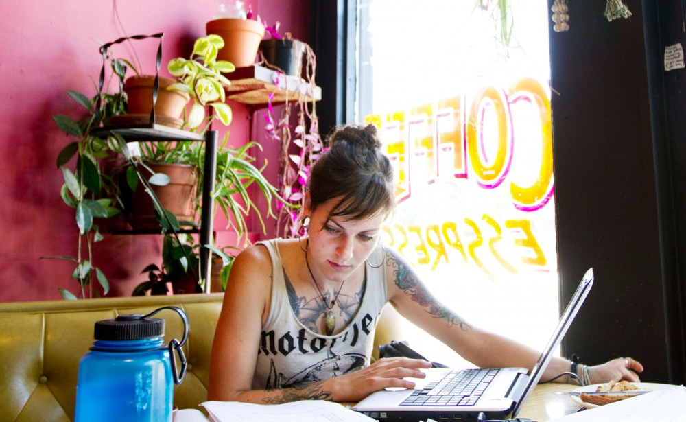 "Ashley Majer, a nutrition undergraduate at St. Catherine University, studies Friday at Hard Times Cafe. Majer says she chooses to study there because she doesn't ""feel so alone when doing homework."""