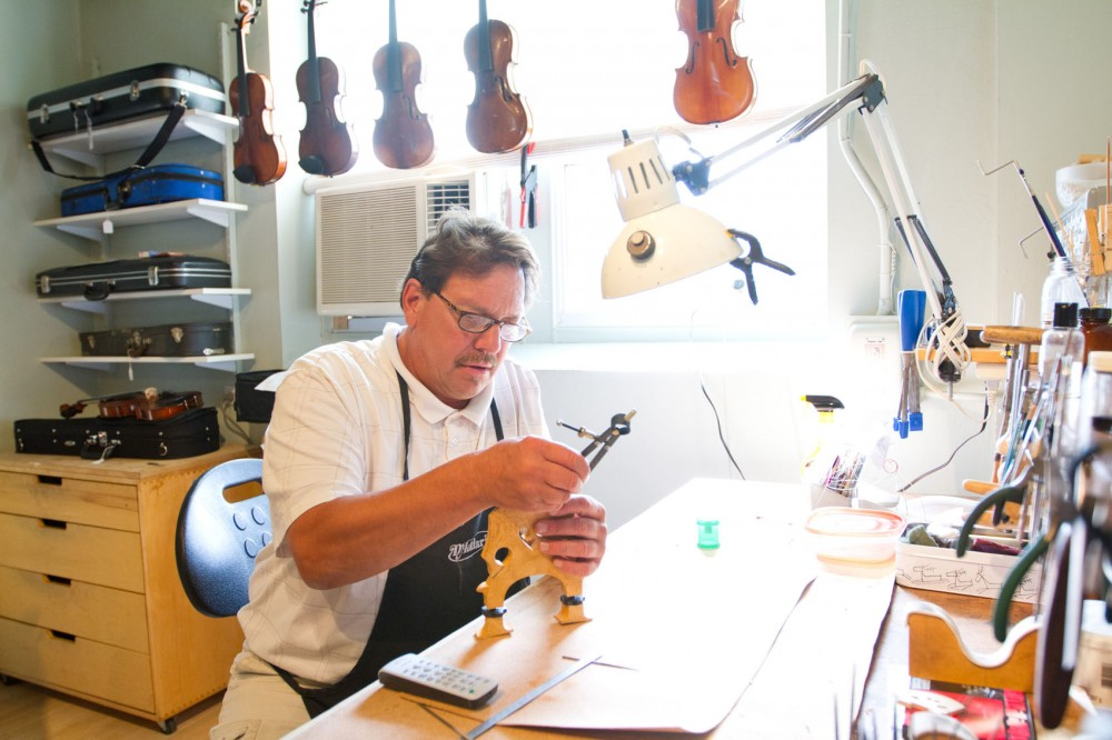 "Luthier Milo Tupy adjusts the bridge of a double bass Friday at Quinn Violins, another building part of the 2010 E. Hennepin Ave. building complex. Quinn Violins sits one floor below what's been rumored as having once been ""Betty Crocker's kitchen."""