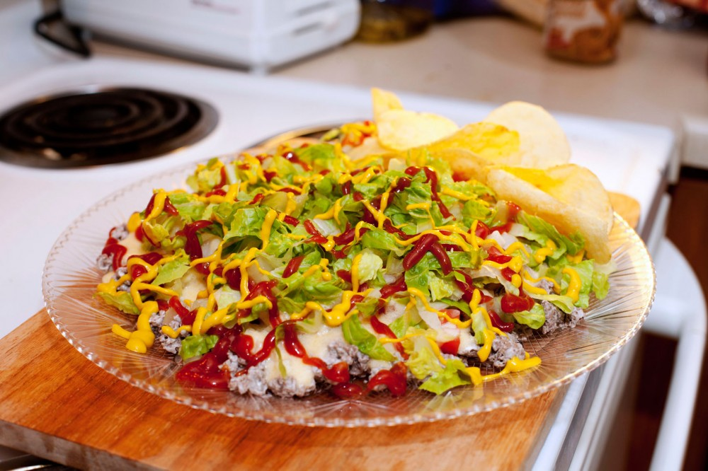 """The """"Seven Days a Beef"""" dip is a great snack that complements a summer picnic or party. The familiar dish is composed of all the ingredients that would make a cheeseburger but is packaged as a nacho-style dip instead."""
