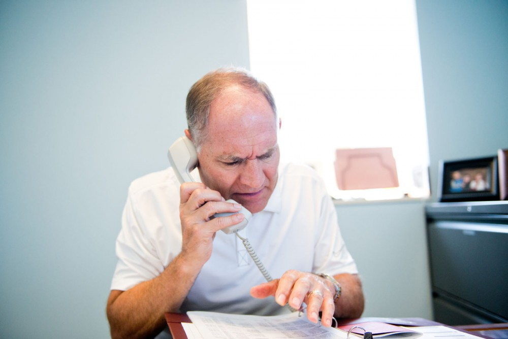 Former athletics director Joel Maturi answers the phone in his office July 23. Maturi now works in the Office of the President.