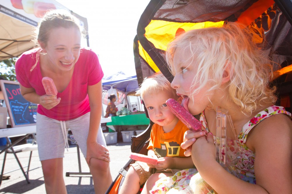 Grace and Jacob Rolek eat JonnyPops merry mountain berry popsicles with their mother, Emily, on Tuesday at the Midtown Farmers Market. JonnyPops was founded in 2011 by five college students and specializes in gourmet popsicles.