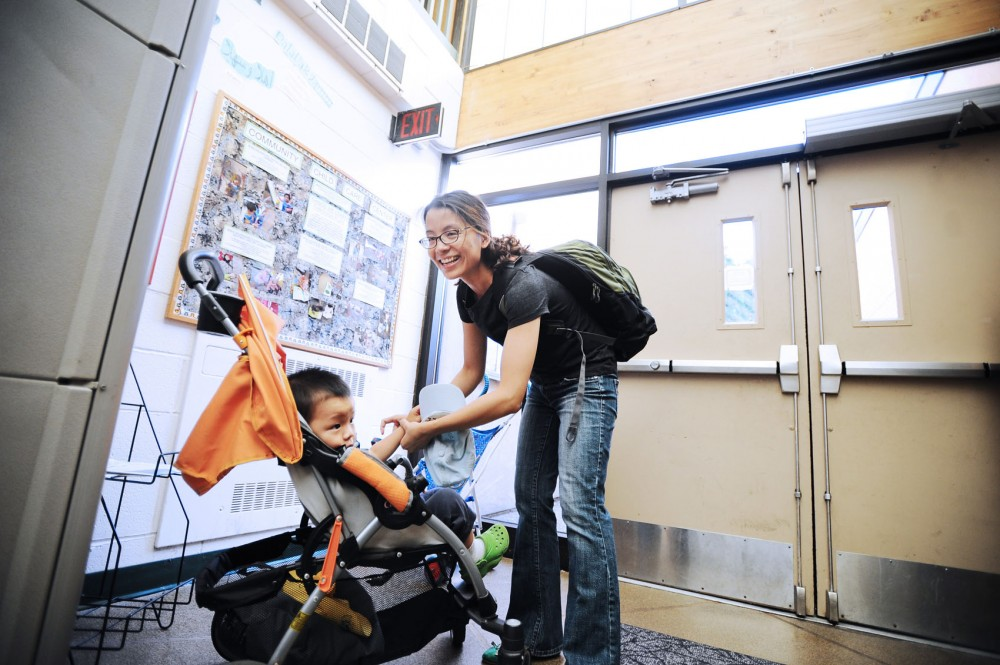 Political science doctoral candidate Zhen Wang drops her son Daniel off at the Community Child Care Center Tuesday morning on the St. Paul Campus. Wang, like other graduate student parents, struggles with childcare costs, relying on savings and family support.