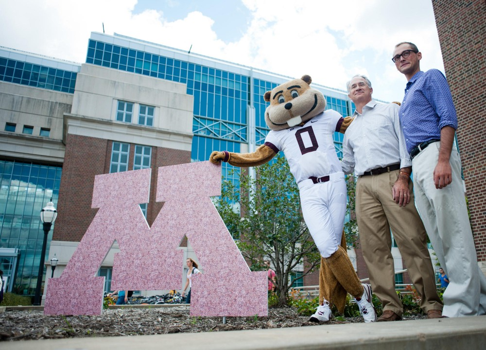 Goldy strikes a pose along with sculptor Nicholas Legeros and his son Alex at the planned site of the Goldy statue Friday in front of Coffman Union.