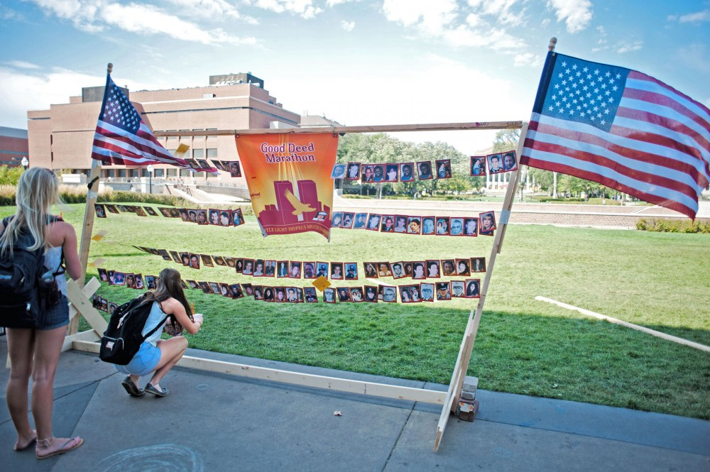 Business freshman Jamie Wyatt, right, pins a photo of a Sept. 11 victim on a memorial organized by the Chabad Jewish student group Tuesday in front of Coffman Union. The memorial was part of a good-deed marathon where students pledged to do good in honor of those who died.