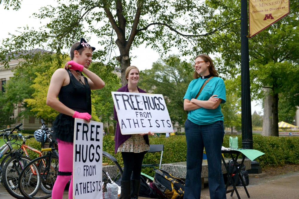 Kate Reuer, campus pastor for the Lutheran Campus Ministry, visits with Andria Bonde, center, and Joshua Brose, both members of Campus Atheists, Skeptics and Humanists. The arrival of Brother Jed prompted many unexpected alliances among student groups with different beliefs.