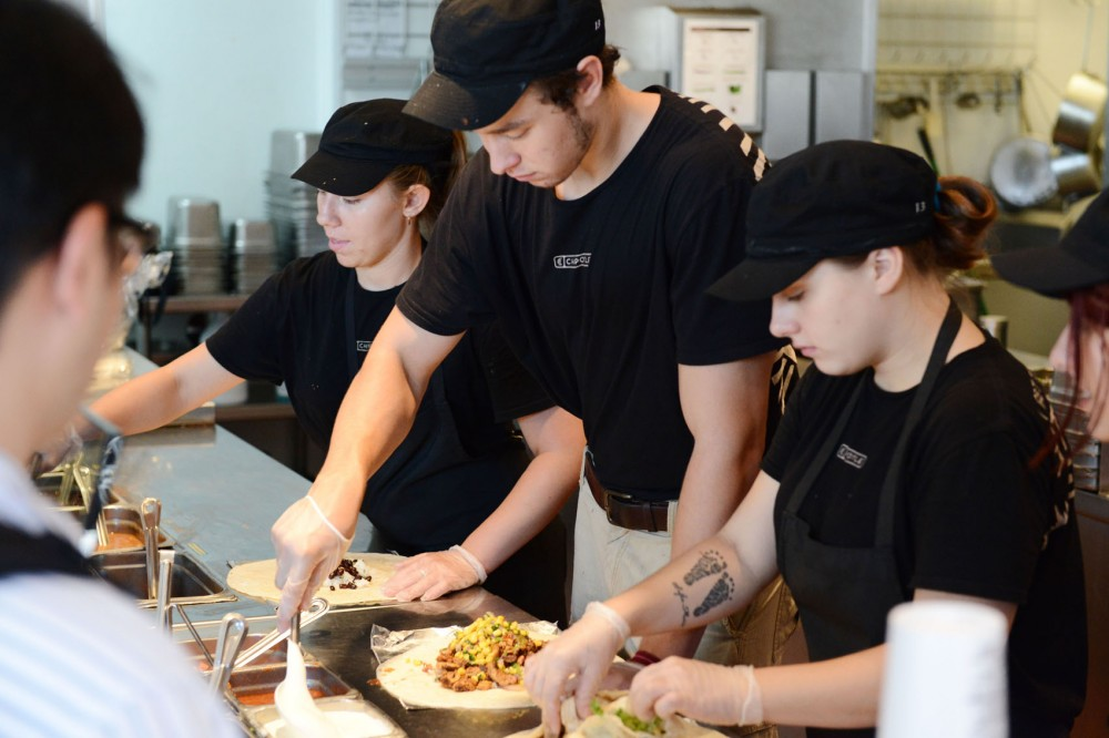 From left, Kayla Casias, John Thome and Ashley Rucinski work on the burrito assembly line at Chiptole on Sunday in Stadium Village.