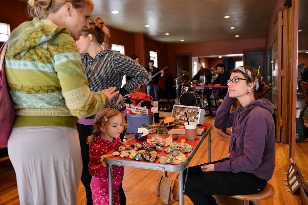 Artist Amanda Rae displays artwork for sale to Liz Hallstein and daughter Mira on Saturday at the Caravan Flea Market in Minneapolis.