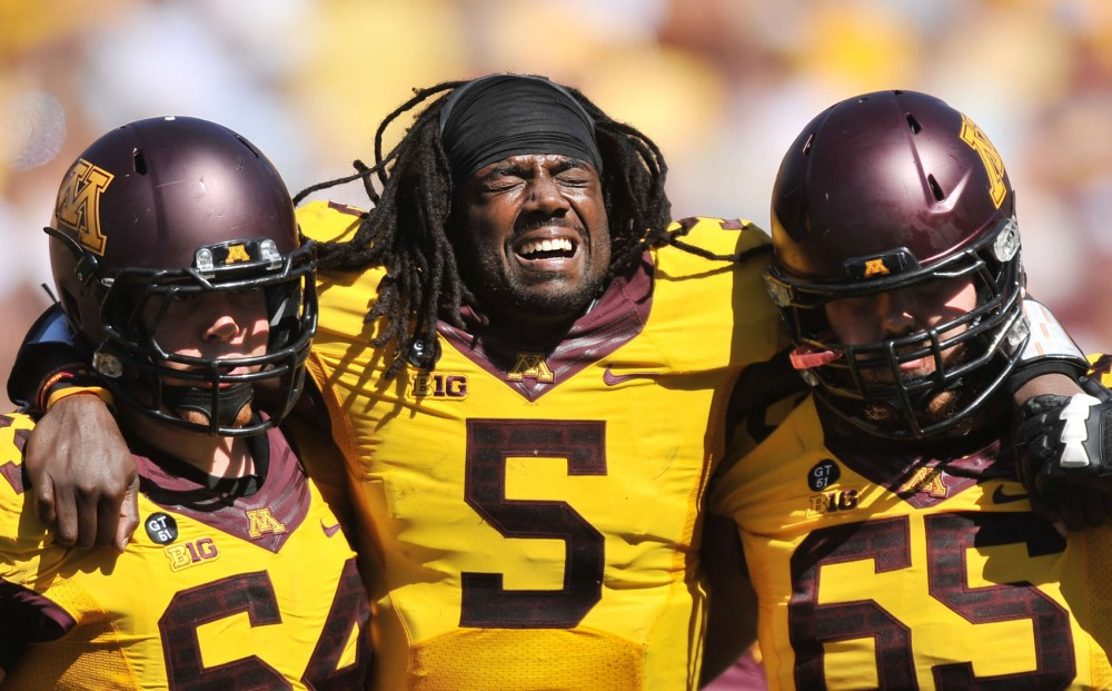 Minnesota quarterback Marqueis Gray, center, is helped off the field by  offensive linemen Caleb Bak and Josh Campion after the starting quarterback suffered a high-ankle sprain in the second quarter.