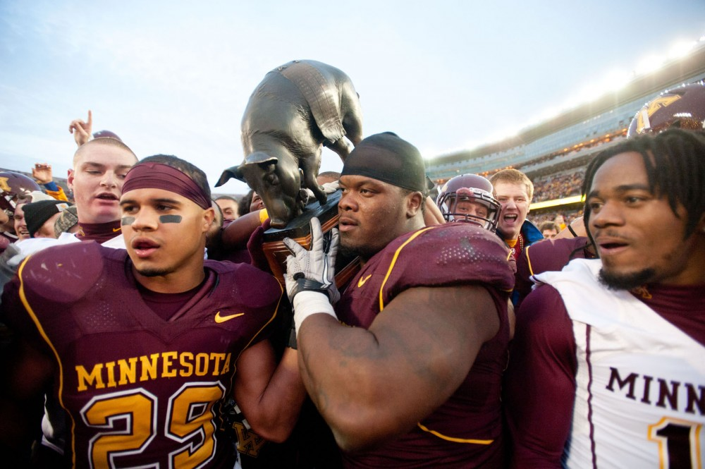 A group of Gophers players hoists the Floyd of Rosedale after Minnesota's win over Iowa in 2011.