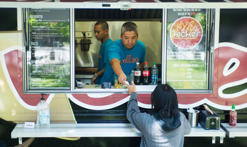 Rick Vang serves a customer at the Vellee Deli food truck Tuesday outside Williamson Hall. Vellee Deli is one of two food trucks that University Dining Service has brought to campus to provide more dining choices in the Knoll area.